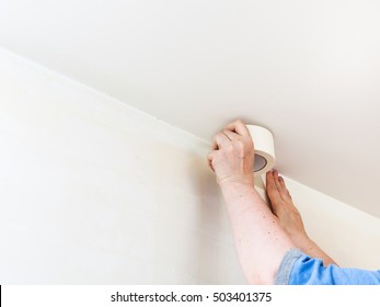 renovation of apartment - preparation of walls for painting. Decorator fixes masking tape on wall before painting