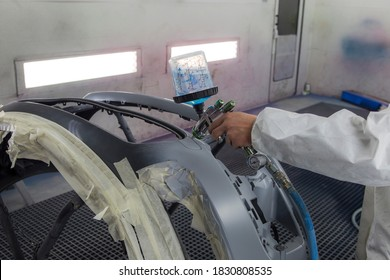 Renovation of bodywork, industrial painting on part of a car. Man working with a machine to spray industrial paint for bodywork renovation.