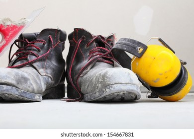 Renovation at home. Construction equipment dirty work boots and yellow protective noise muffs in building site.