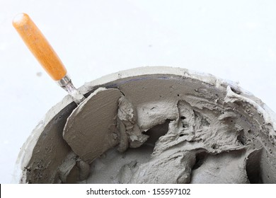 Renovation at home dirty trowel and bucket with mortar on construction building site