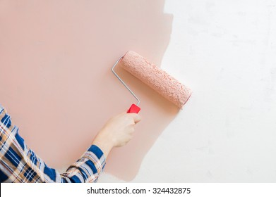 Renovation of interior. Painters hand holds paint roller and painting wall with pink color.