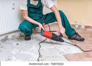 Renovation of old floor. Demolition of old tiles with jackhammer.
