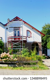 Renovation, outside painting of traditional Dutch house and scaffold, Netherlands