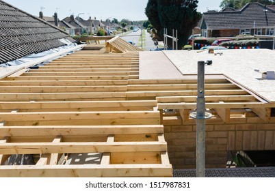 Renovation projects. Building of extension of the existing house, unfinished wooden roof structure, brick walls, view from scaffoliding, selective focus