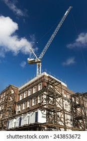 Renovation of red brick building with crane and scaffolding. Material storage containers.