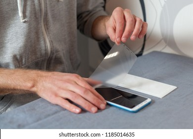 Renovation, repair concept. Preparing the screen for gluing new accessory 3d protective glass. High angle top side profile view man removes the matte protective film on the digital device or phone