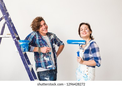 Renovation, repair and people concept - Young married couple painting walls in their new home.