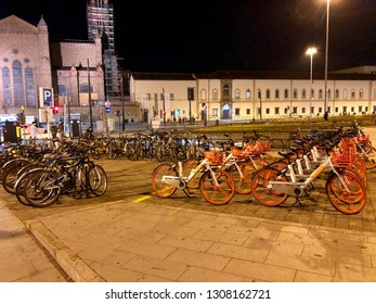 Rent of orange bikes, bike Sharing MoBike - A bike parking in front of Firenze Santa Maria Novella trains station, Florence, Italy 28/01/2019   Italy bike sharing