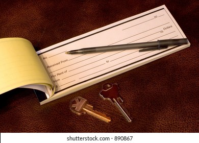 A rent receipt book with keys and a pen on a leather desk top