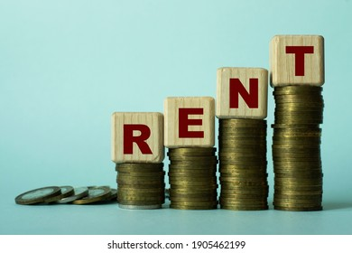 RENT - word on wooden cubes. Which stand on stacks of coins on a light background. Business concept