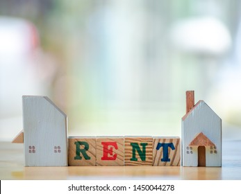 Rent word written cube with hand holding home on wooden background. Concept for loan, property ladder, financial, mortgage, real estate investment, taxes and bonus.