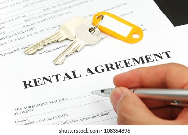 rental agreement form with signing hand and keys and pen