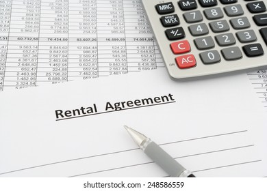 rental agreement with numbers, calculator and pen