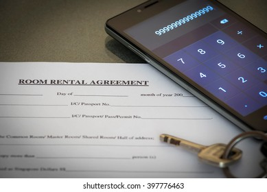 rental agreement with room key and smartphone calculator