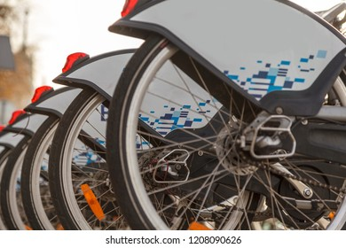 A rental bicycles stand in a row on a parking.Group of bicycles in the row.