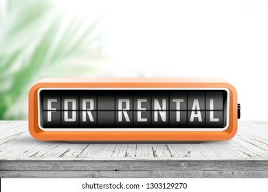 For rental text on an analog device in orange color in a bright room with a tropical plant
