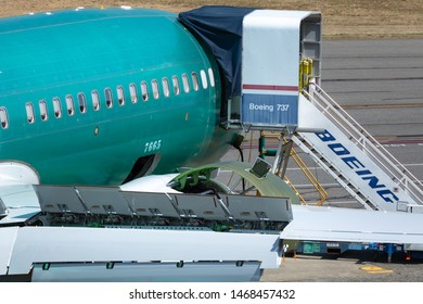 Renton, Washington / USA - July 31 2019: New airplane with Boeing 737 access stairs, at the 737 MAX airliner factory in Renton, with wing hydraulics in the foreground