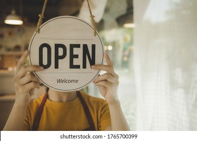 Reopen. waitress woman turning open sign board reopen after coronavirus quarantine is over in modern cafe coffee shop ready to service, cafe restaurant, small business owner, food and drink concept - Shutterstock ID 1765700399