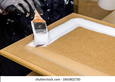 Repainting kitchen cabinet doors with white chalk paint indoors at home. Giving old kitchen new look concept. Hand holding a paint brush tool with paint against old cupboard door.