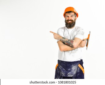 Repair advertisement concept. Builder, plasterer, repairman, foreman in helmet holds hands crossed, white background. Man with smile holds putty knife or tool, points with index finger, copy space.