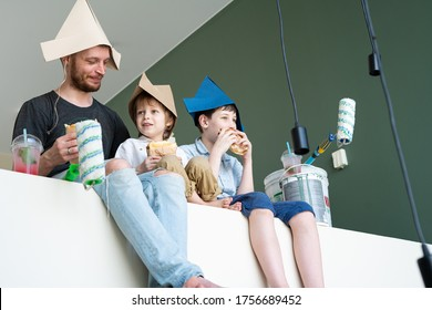 Repair in the apartment. A father and his two sons paints the wall and taking a lunch break. Happy boys renovating their new home and taking a lunch break