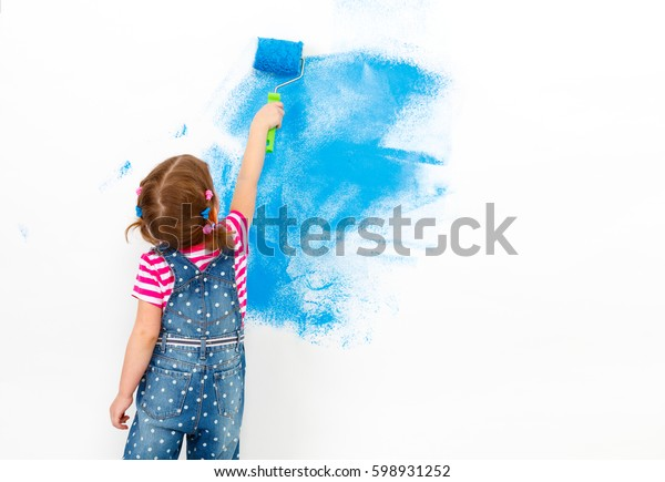Repair in the apartment. Happy child girl paints the wall with blue paint
