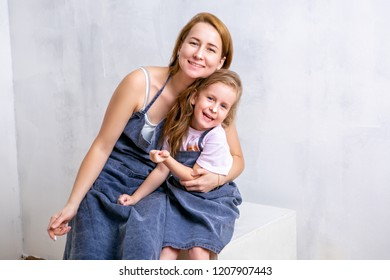 Repair in the apartment. Happy family mother and daughter in aprons paint the wall with white paint. Mother and daughter smeared each other with paint and laugh. portrait