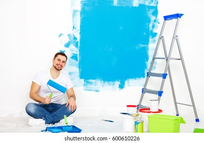 Repair in the apartment. Happy man paints the wall with blue paint