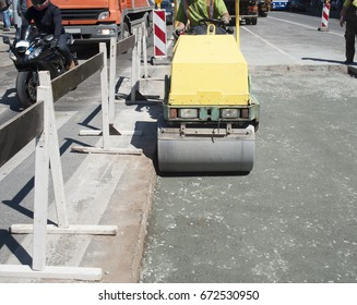 Repair of asphalt pavement on the busy city road. Tamping the gravel with a roller for asphalt