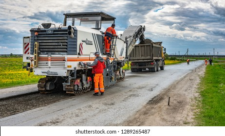 Repair of asphalt pavement of the road, Tyumen, Russia: June 9, 2018. Road cold milling machine removes the old asphalt and loading into a dump truck.