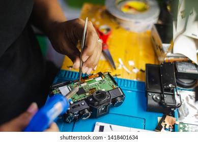 Repair broken digital DSLR camera service center,hand of male technician repairing Camera,The camera is disassembled during the repair process.