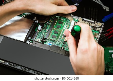 Repair a broken laptop with details and special tools on a black desk. Work process of the repairman. The pieces of computer