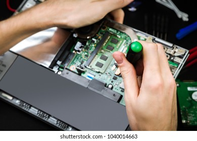Repair a broken laptop with details and special tools on a black desk. Work process of the repairman