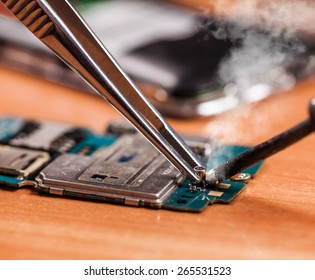 repair a broken mobile phone closeup on wooden background
