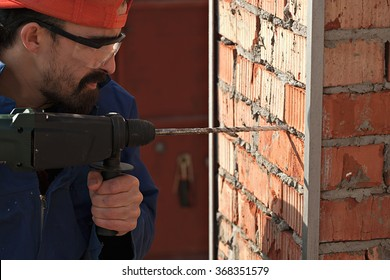 Repair, building concept - close up of male with electric drill perforator making hole in brick wall