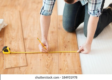 repair, building and home concept - close up of male hands measuring wood flooring