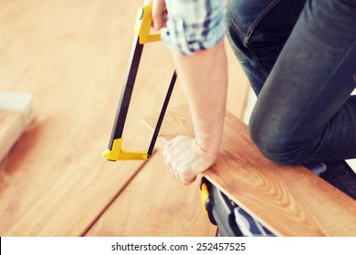 repair, building and home concept - close up of male hands cutting parquet floor board with saw