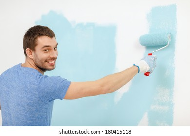 repair, building and home concept - smiling man painting wall at home