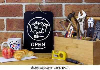Repair cafe sign on chalk board on table with tools and coffee mug, sustainable living concept the right to repair consumer goods to reduce waste