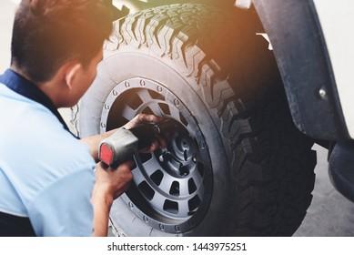 Repair or changing tire car pickup mechanic screwing unscrewing car wheel at repair service station automobile shop