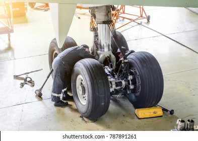 Repair of the chassis landing gear of the aircraft, two technicians of mechanics at work in the hangar