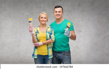 repair, construction and maintenance concept - smiling couple with paintbrush