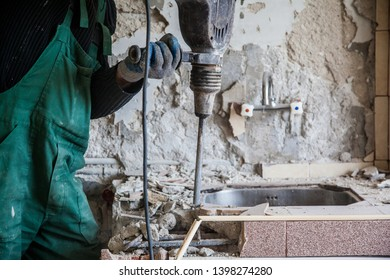 Repair and construction working indoors. Drill puncher breaks the old sink