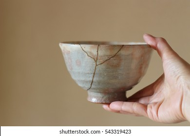 Repair of crack pottery hagi tea cup with a hand