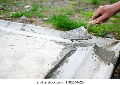 repair cracked concrete close-up a man's hand with a spatula