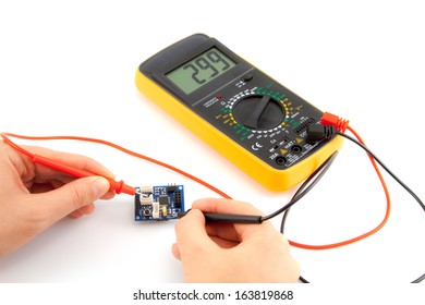 Repair of electronics with digital multimeter in the white background
