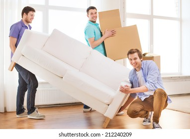 repair, furniture, decorating and home concept - smiling friends with sofa and cardboard boxes