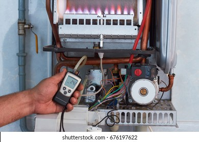 Repair of a gas boiler, setting up and servicing by a service department. Adjustment of gas pressure by manometer