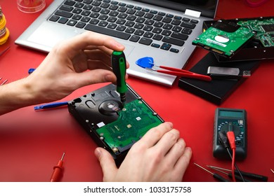 Repair a hard drive with a laptop and special tools on a red table. Workplace of repairman.