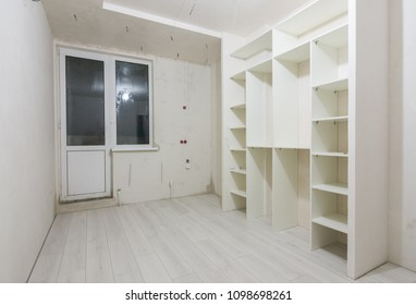 Repair in the living room of new buildings, built-in wardrobe and on the floor laminated panels
